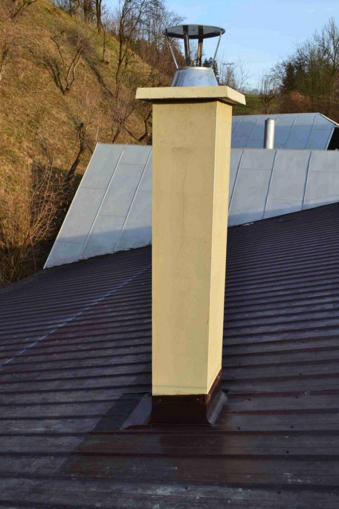 komín slabožltý na streche čiernej farby