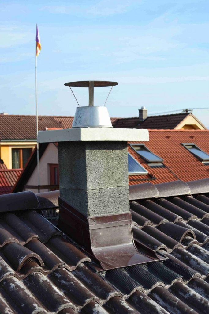 olemovaný komín v profilovanej betónovej škridle so strechami v pozadí