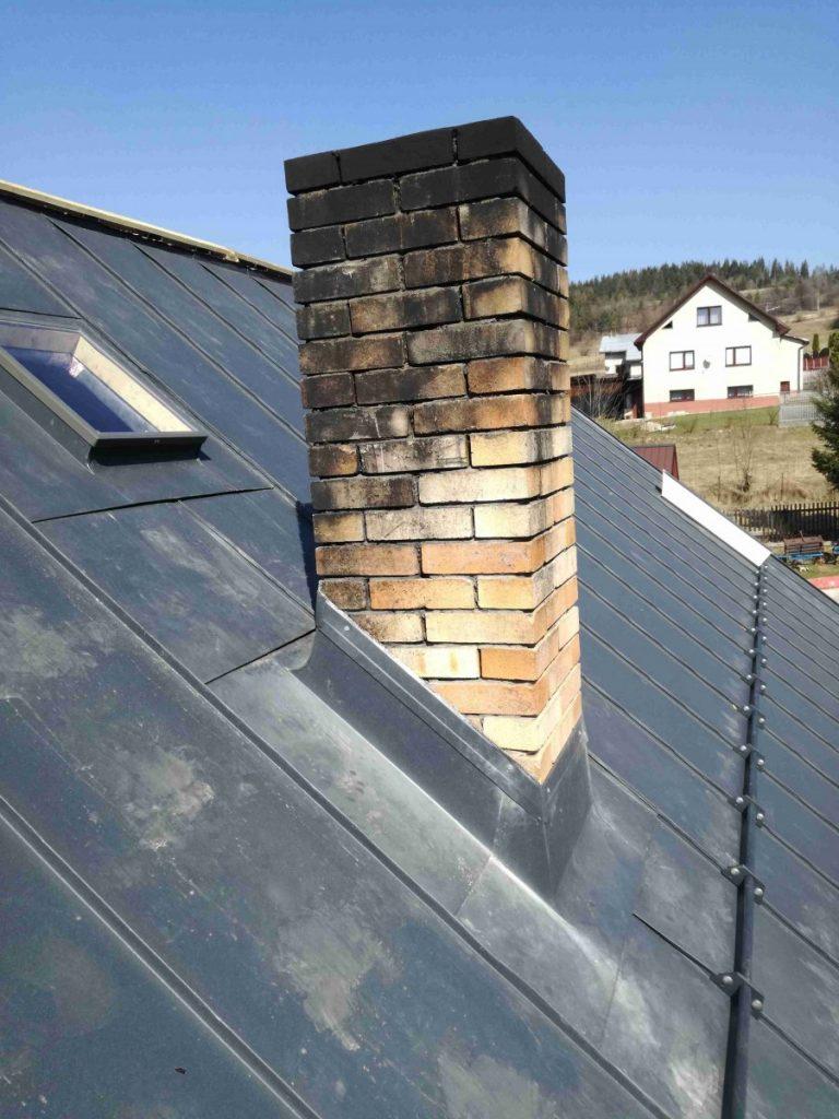 olemovaný komín na streche z falcovanej krytiny s bielym domom v pozadí