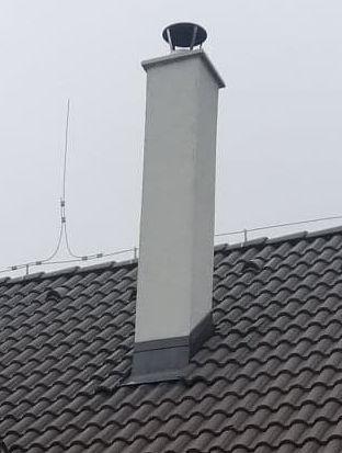 oplechovaný vysoký komín bielej farby na čiernej streche